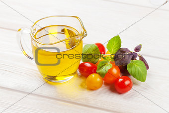 Olive oil, tomatoes, basil on wooden table