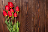 Red tulips bouquet over wood