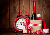 Christmas gift, alarm clock, santa hat and champagne