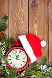 Christmas wooden background with clock, fir tree and santa hat