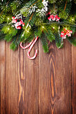 Fir tree branch with christmas lights and candy canes on wood