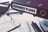 Business Plans on Ring Binder. Blured, Toned Image.