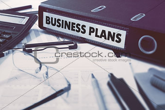 Business Plans on Ring Binder. Blured, Toned Image.