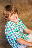 Happy Boy Child Sitting Smiling on Hay Bales
