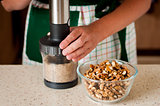 A Woman Chopping Walnuts in a Food Processor
