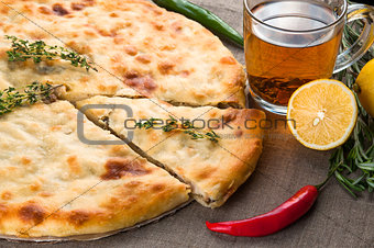 Top view of calzone pizza or chicken mushroom pie with pepper, lemon, rosemary and tea on linen fabric background