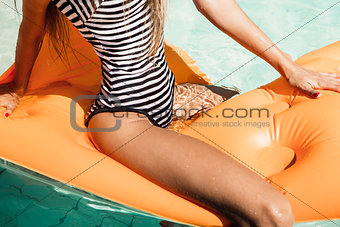 sexy young woman in a swimsuit sits astride on an inflatable mat