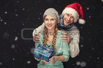 Happy Couple in Santa's Hat with New Year Gift