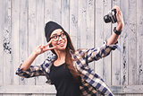 Hipster girl in glasses making selfie