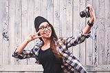 Hipster girl in glasses making selfie