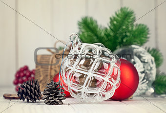 Christmas balls with branch fir and pinecone on wooden board