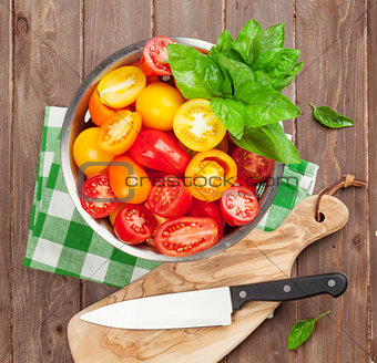 Fresh colorful tomatoes and basil in colander
