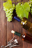 Bunch of grapes, white wine bottles and corkscrew