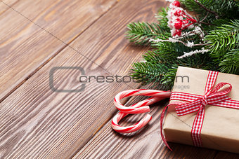 Candy cane, gift box and christmas tree on wooden table