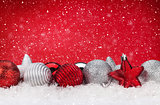 Christmas red background with baubles in snow