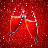 Two champagne glasses over red christmas background