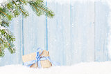 Christmas gift box and fir tree branch in snow