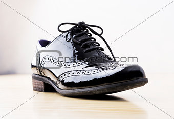 Footwear Concept. Horizontal Image. Black female classic leather shoes on the desk