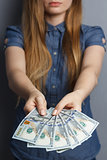 Fan of 100 dollar banknotes in woman hands