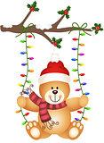 Teddy bear swinging on Christmas lights