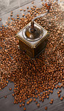Old vintage coffee grinder on roasted hot beans with smoke