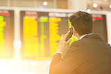 Businessman looking at airport flight timetable