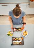 Woman in kitchen preparing halloween trick or treat