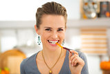 Smiling young woman eating halloween gummy worm candy
