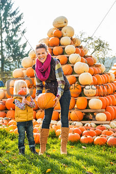 Beautiful woman with little girl holding pumpkins on farm