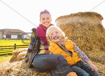 Portrait of beautiful woman and cute girl sitting on hay on farm
