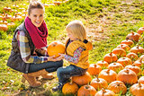 Smiling woman and child choosing a pumpkin on farm