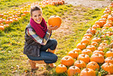 Portrait of smiling woman choosing pumpkin on farm
