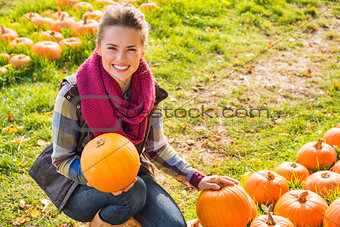 Portrait of smiling woman holding pumpkins on farm