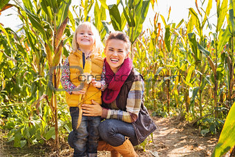 Portrait of happy mother and child staying in corn field on farm