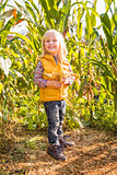 Portrait of cute smiling child in the corn field on farm