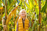 Little smiling blond kid staying in a corn field on farm
