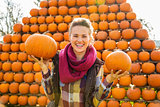 Portrait of smiling woman holding pumpkins in autumn outdoors