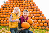 Smiling woman and girl holding pumpkins in autumn outdoors