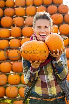 Portrait of smiling beautiful woman holding pumpkins on farm