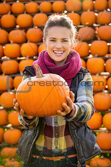 Portrait of smiling beautiful woman holding pumpkins on farm