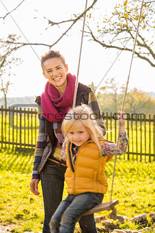 Portrait of smiling woman and swinging child in autumn outdoors