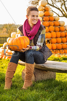 Portrait of woman sitting on the bench with pumpkin on farm