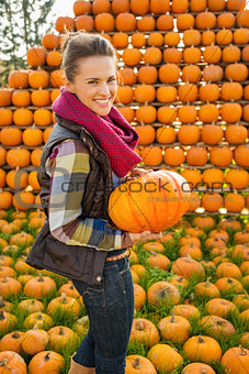 Portrait of smiling woman holding pumpkin on farm