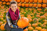 Portrait of smiling woman sitting and holding big pumpkin