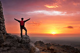 Man on top of a mountain victorious admiring the sunrise - 2