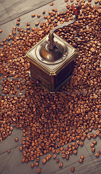 Old vintage coffee mill on roasted hot beans