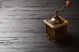 Old bronze coffee grinder on black wooden board
