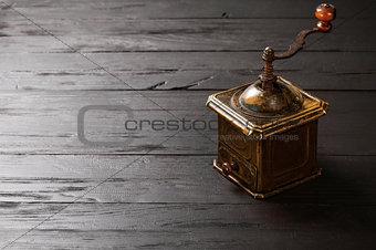Old bronze coffee grinder on black wooden board