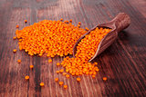 Red lentils on wooden scoop.