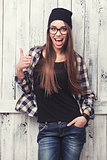 Hipster girl in glasses and black beanie with thumbs up